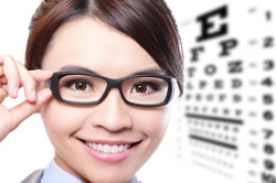 A woman in glasses, in front of an eye chart