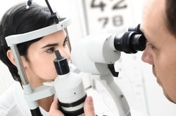 An eye doctor examines a patient's eye with a camera.